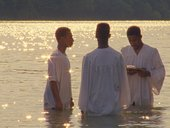 A film still with three men standing in the water for a baptism at sunset