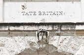 Photograph of a close up of Tate Britain's building showing a damaged head statue with wording 'Tate Britain' above it