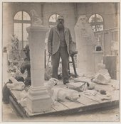 Rodin standing in his studio among plaster casts, black and white photograph