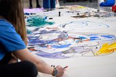 A young person creates art on a large canvas on the floor