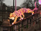 Neon tiger climbing down stairs at the front of Tate Britain