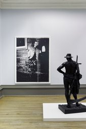 Photograph of two artworks in a gallery - a sculpture of a dark figure, hand on hip, holding a large scythe in the right-foreground and a large photographic work on the far wall, a black-and-white glitchy image of a punk figure