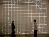 Two people stand in front of a projected wall