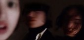 Out-of-focus photograph of three performers' faces in a dark environment