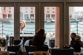 2 people are sat on sofas having drinks on a coffee table. Behind there are large windows which look onto the water in the Albert Dock.