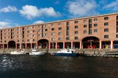 tate liverpool on the albert dock as seen from across the water. there are boats in the water and the sky is blue.