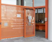 Entrance to Tate Liverpool. A glass door is open with a bright orange frame.