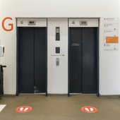 a set of lifts with signage on the floor showing where you can stand.