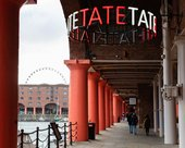 The Albert dock outside of Tate liverpool with a Tate sign.