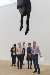 A group looks up at a hanging artwork