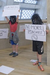 two young people wearing guerrilla masks holding up signs