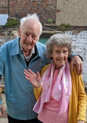 An elderly couple smile and wave at the camera