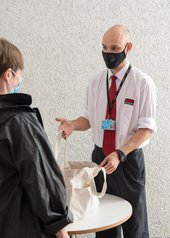 A member of security staff checking a visitors bag.