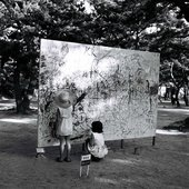 Two girls draw on a board outside in a dense woodland in a park