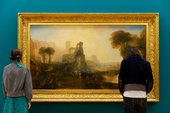 two people stand in front of a Turner painting