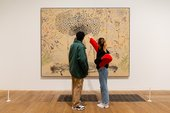 two visitors stand and look at a painting, there is a barrier around it