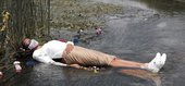 photo of a woman lying in a river with a surgical mask on