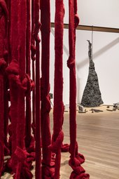 Red strips of fabric hang down in the foreground while a large irregular piece of forged metal hangs in the background