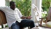 Portrait of Meshac Gaba sitting in a chair talking in a studio