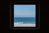 view of a blue sky, sea and sandy beach seen through a square window