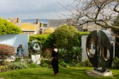 a woman stands in the Barbara Hepworth garden looking out to the view