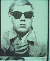 Portrait in green and black of Andy Warhol wearing sunglasses