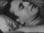 Black and white film still of a man sleeping