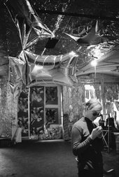 Black and white photograph of Andy Warhol stood below some inflated foil shapes