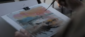 a person paints a watercolour sunset