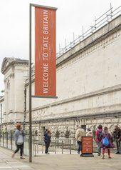 the sSide entrance view of Tate Britain at the top of a ramp with a sign that reads 'welcome to Tate Britain'