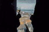 Two people silhouetted against the view from the cafe at Tate St Ives holding glasses of wine