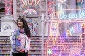 Chila Kumari Singh Burman stands in front of her artwork at Tate Britain