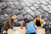 Art handlers wearing gloves gather round an artwork in a box