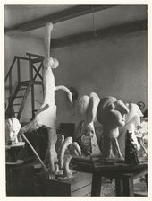 A black and white photograph of sculptures in a studio