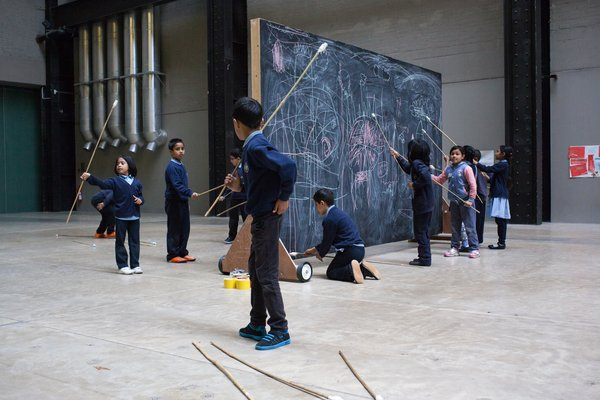 Children drawing on a blackboard in the Turbine Hall