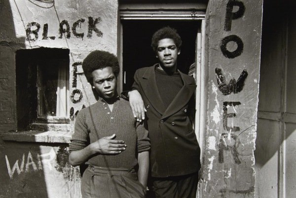Two black men outside a house with the words BLACK POWER written on the exterior