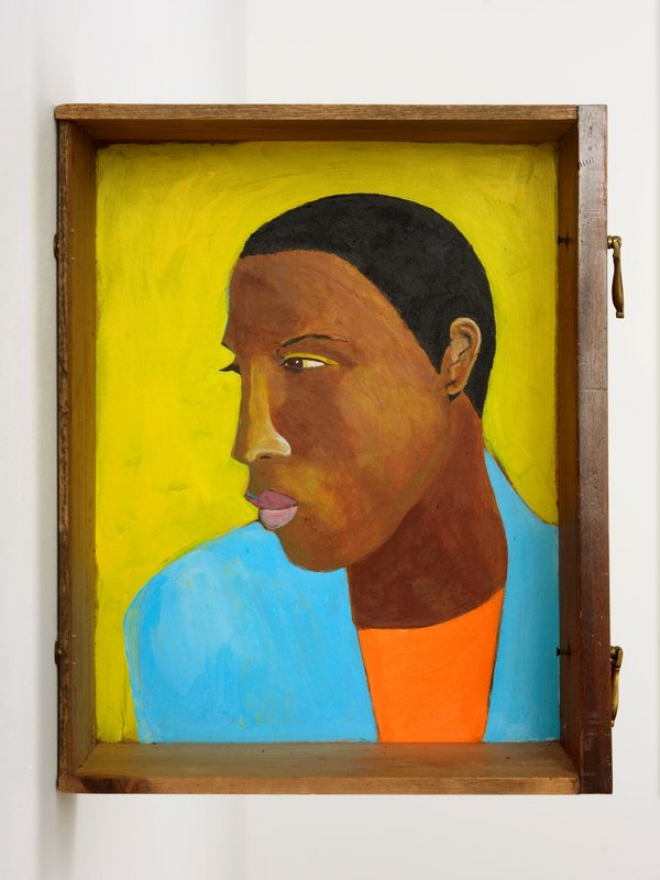 painted portrait of a man wearing a turquoise shirt placed inside a wooden drawer