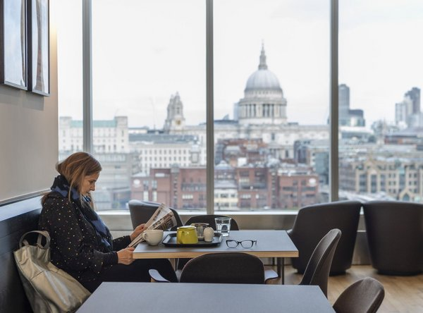 A Woman Sits And Reads Book With St Pauls In The Background
