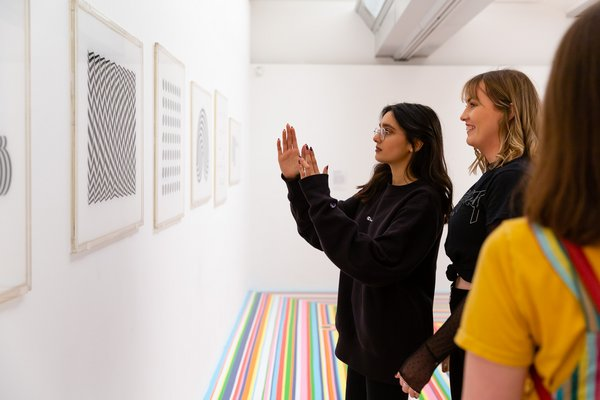 2 people are stood on a brightly coloured striped floor. They are looking at a series of artworks hung and framed on the wall.