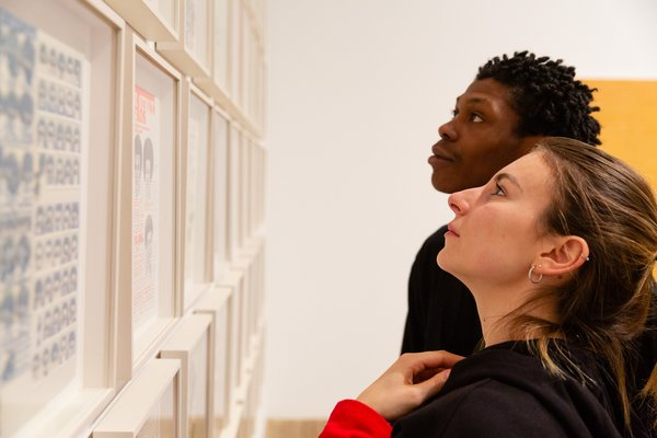 a close up of two people looking a a wall of framed artworks
