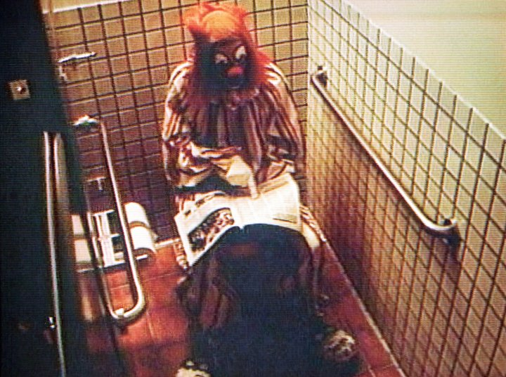 A clown sat in a toilet reading a newspaper