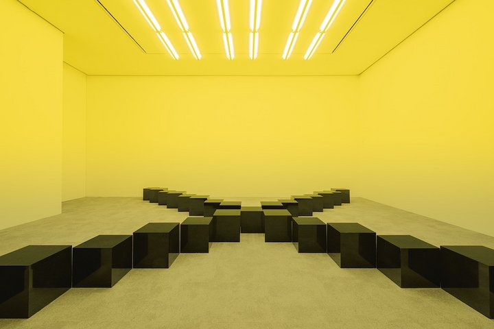 A series of black marble squares places in a cross formation in a room lit with yellow light