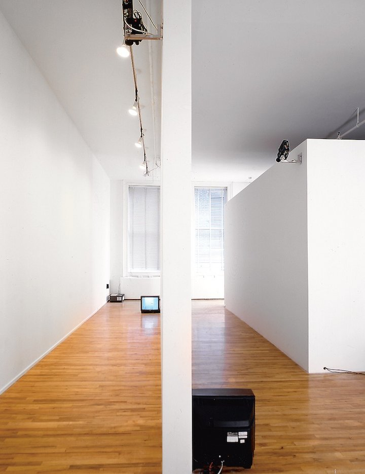 A TV monitor places on the floor in a white corridor