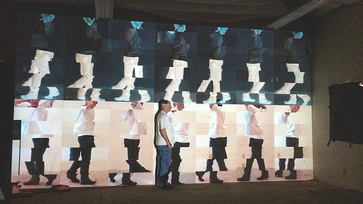 Image of a man walking past a projection of himself repeated multiple times