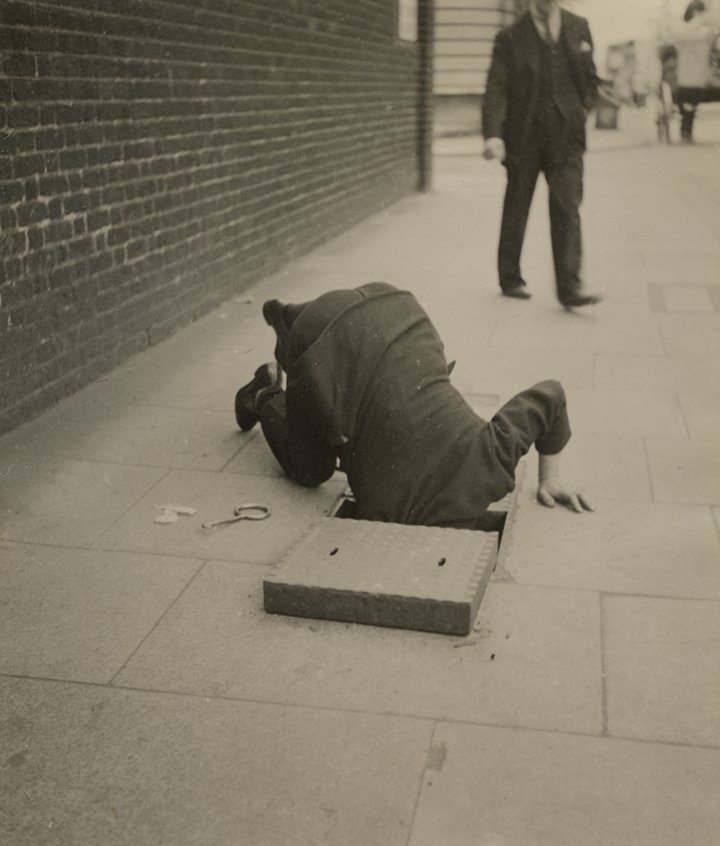 Black and white photograph of a man looking inside a sidewalk inspection door in London pavement