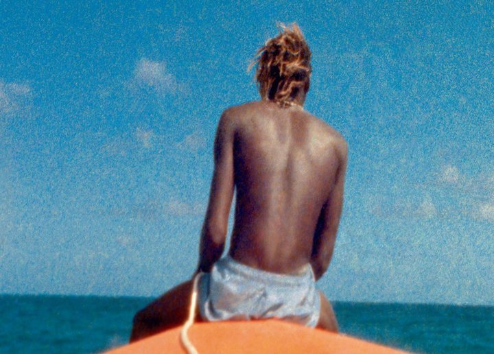 Still from McQueen film showing the back on a man sat on a surf board against a blue sky