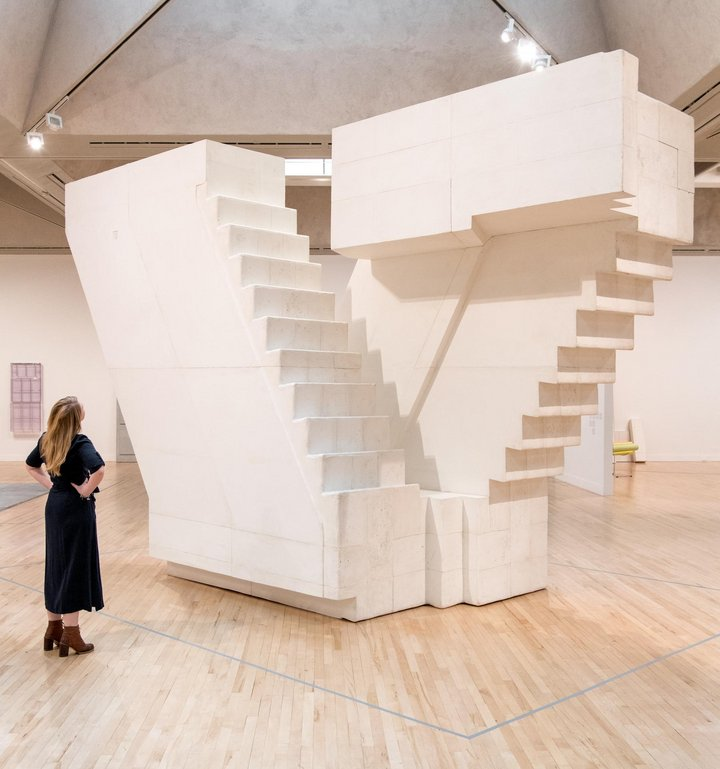 cast of some stairs in a warehouse with a woman standing in front of it
